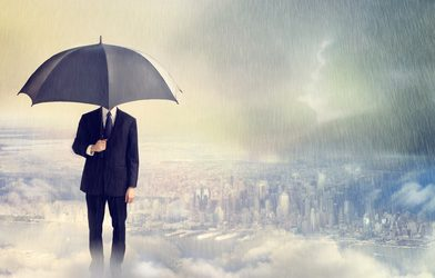 Business Man with Umbrella Above the City